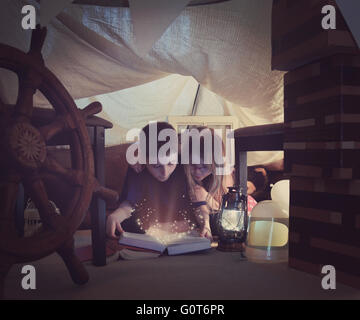 Two young children are reading a book together with sparkles in a tent fort at home for a storytime or learning - Stock Photo