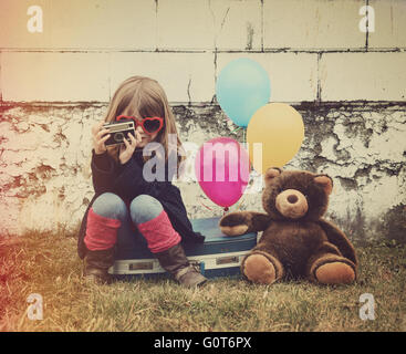 A photo of a vintage child taking a picture with old camera against a brick wall, balloons and a teddy bear for - Stock Photo