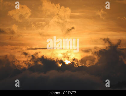 Partial of sun appear behind the dark cloud with golden sky as background - Stock Photo