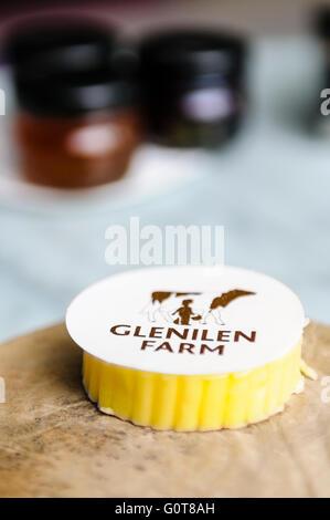 A piece of Glenilen Farm Irish cream butter on a wooden bread board with jams in a hotel restaurant. - Stock Photo