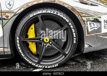 Yellow standard brake calipers on a Ferrari. - Stock Photo