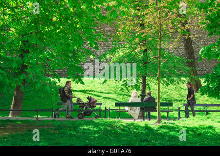 People park summer, view on a summer morning of people walking along a tree-lined path in Planty Park, Krakow, Poland. - Stock Photo