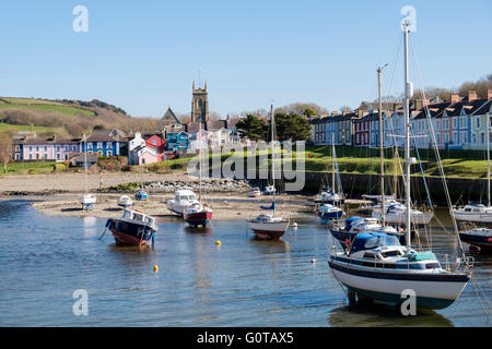 Looking along Afon Aeron River estuary to church with boats moored in harbour on incoming tide in pretty town of - Stock Photo
