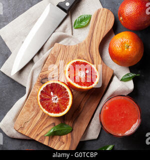 Fresh ripe red oranges and juice on stone table. Top view - Stock Photo