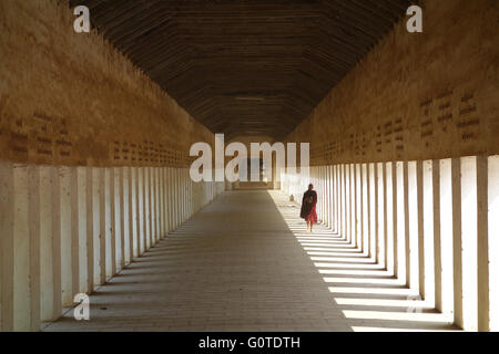 Buddhist monk walking down a corridor - Stock Photo