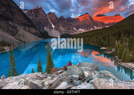 A young couple at Moraine Lake by sunrise. Banff National Park, Alberta, Canada. - Stock Photo