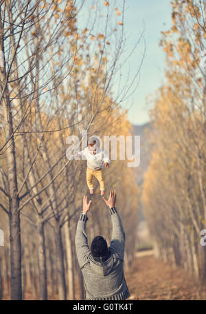 Man throwing baby girl in the air - Stock Photo