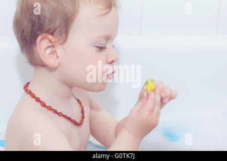 Portrait of a boy playing with plastic toy in the bath - Stock Photo