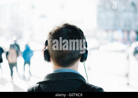 Rear view of hipster man wearing headphones - Stock Photo