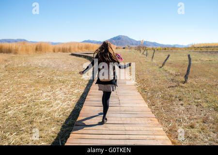 Rear view of a woman walking along wooden walkway, Xinjiang, China - Stock Photo