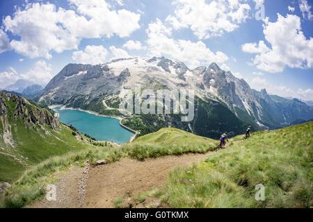 Man and woman riding mountain bikes along trail, Dolomites, Italy - Stock Photo