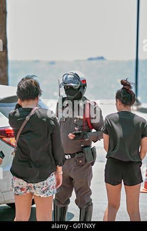 Thai police officer questioning female drivers involved in the collision of two vehicles. Thailand S. E. Asia - Stock Photo