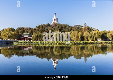 The white tower and its reflection in Beihai lake. Photo shot in autumn of 2014 in Beihai Park in Beijing, China. - Stock Photo