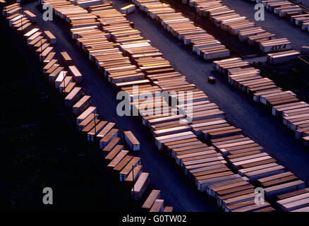 Aerial sunset view of rows of tractor trailers lined up in shipping depot - Stock Photo