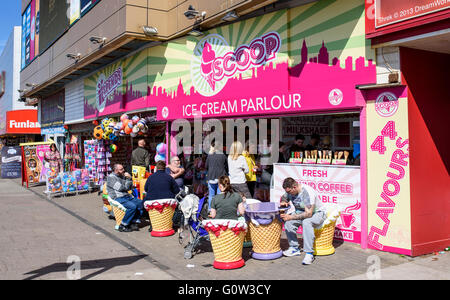 People enjoying ice cream at the Scoop ice cream parlour on the promenade in Blackpool, Lancashire, UK - Stock Photo