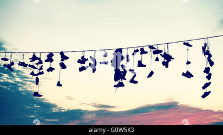 Retro stylized silhouettes of shoes hanging on cable at sunset, teenage rebellion concept. - Stock Photo