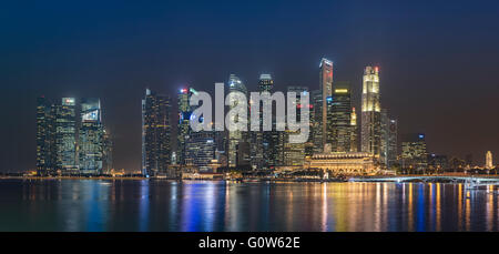 The Skyscrapers of Singapore Financial District at Raffles Place overlooking Marina Bay in the Evening - Stock Photo
