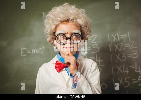 Boy standing in front of blackboard - Stock Photo