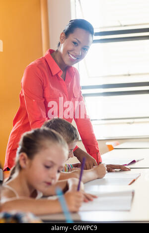 Teacher standing and posing while pupils are working - Stock Photo
