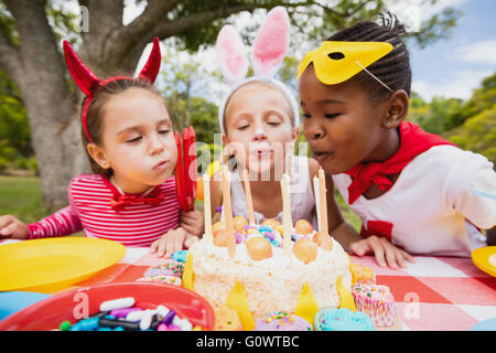 Three little girls blowing together birthday candles - Stock Photo