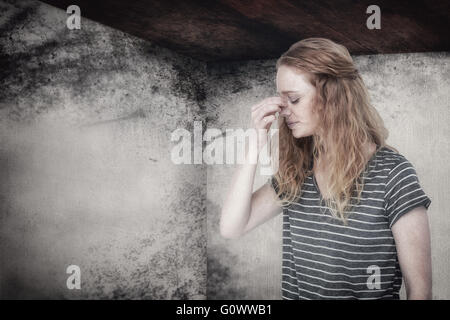 Composite image of blonde woman with headache pinching her nose - Stock Photo