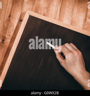 Composite image of hand writing with chalk - Stock Photo