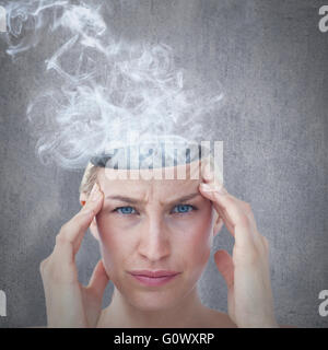Composite image of pretty blonde suffering from headache looking at camera - Stock Photo