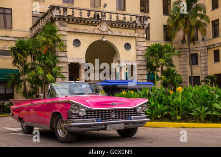 A red oldtimer drives in front of Havanas infamous Hotel national which retains the charm of the Golden 20s - Havana, - Stock Photo