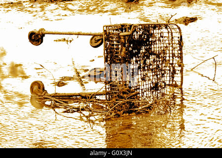 DRAMATIC SHOT OF DUMPED SUPERMARKET TROLLEY IN A RIVER - Stock Photo