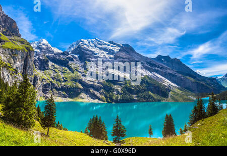 The panorama in summer view over the Oeschinensee (Oeschinen lake) and the alps on the other side near Kandersteg - Stock Photo