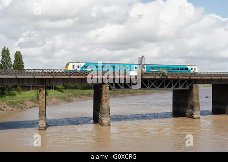The River Usk in Newport Wales, with Arriva commuter train passing over. - Stock Photo