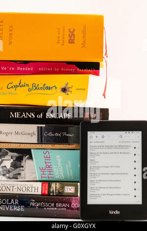 Amazon Kindle turned on leaning against stack of paperback books with titles, to show the amounts of reading material - Stock Photo
