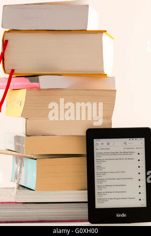 Amazon Kindle turned on leaning against stack of paperback books to show the amounts of reading material that can - Stock Photo