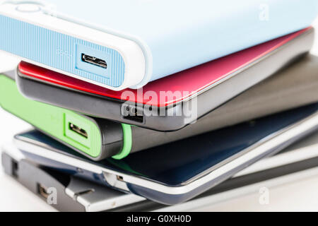 Five different and various coloured external portable hard drivers stacked up showing end with USB connection points. - Stock Photo