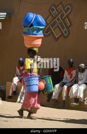 Curious image about woman carrying basins and eating. Zinder. Niger - Stock Photo