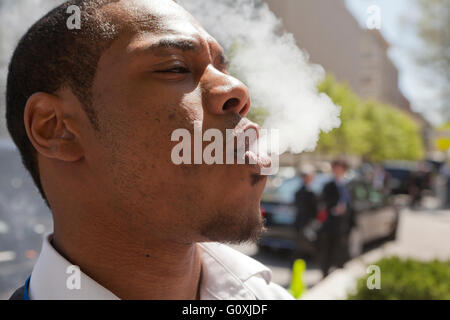 Young African-American man blowing vapor - USA - Stock Photo