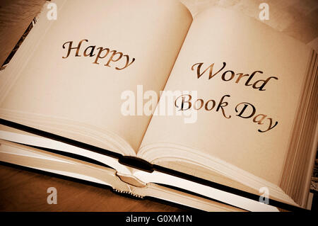 sentence happy world book day, celebrated each year on april 23, written on an open book - Stock Photo