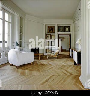Spacious, open plan living room with parquet flooring and  a mix of traditional features and contemporary furniture. - Stock Photo