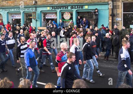 dh Ba game KIRKWALL ORKNEY Ba team walking Kirkwall street to start of Ba game - Stock Photo