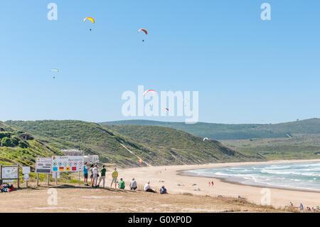 KNYSNA, SOUTH AFRICA - MARCH 3, 2016: Paragliders in the air with spectators watching at a beach in Buffelsbaai - Stock Photo