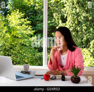 Mature woman, wearing pink bathrobe, working from home in front of large window with bright daylight and trees in - Stock Photo