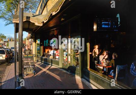 Patrons enjoy open window sunset dining at The Tenn Sixteen Food & Drink Co., in trendy East Nashville, TN - Stock Photo