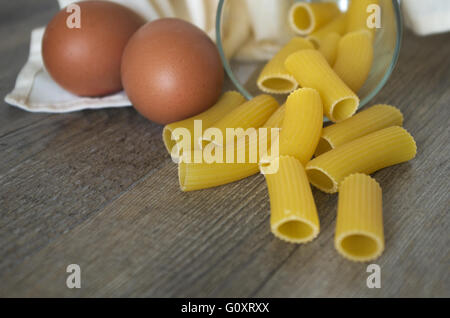 Italian food. Pasta (rigatoni) with eggs on wooden table in low light - Stock Photo