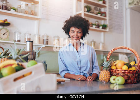 Portrait of beautiful young woman standing at counter in juice bar smiling to camera. African female juice bar owner. - Stock Photo