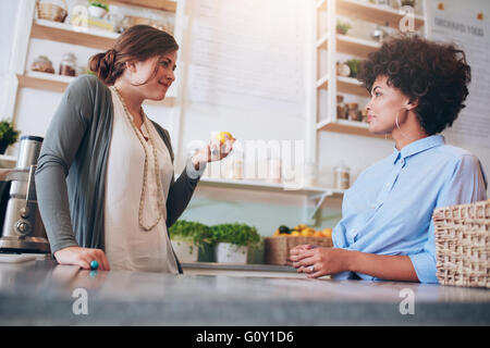 Two young female employees standing behind juice counter and walking. Juice bar owner talking with female employee. - Stock Photo