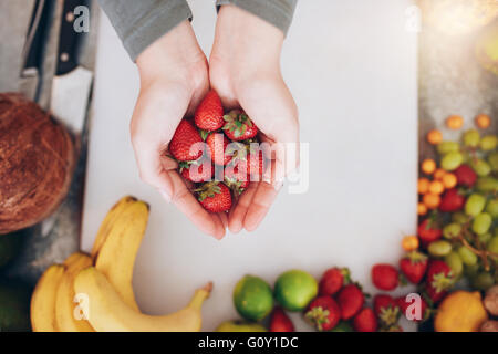 Top view close up shot of a woman's hands holding fresh strawberries over shopping board with fruits. Female holding - Stock Photo