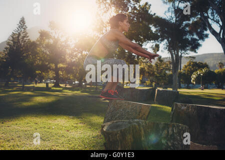 Shot of a young woman jumping onto wooden log at the park. Sportswoman doing exercise in nature on a sunny day. - Stock Photo