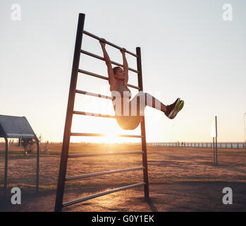 Full length shot of young woman exercising on wall bars with her legs up. Fitness woman exercising her abs with - Stock Photo