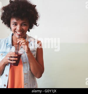 Portrait of happy young african woman having a fresh fruit juice. Young female model drinking juice with straw. - Stock Photo