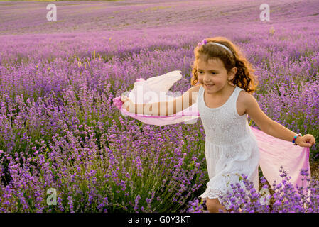 Girl running through a lavender field, Kazanlak, Bulgaria - Stock Photo